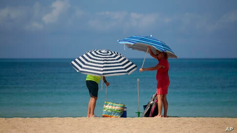 A couple adjust sunshades at the beach of Palma de Mallorca, Spain, Tuesday, June 16, 2020. Borders opened up across Europe on…