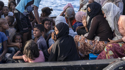 Ethnic Rohingya people sit on the deck of a boat off North Aceh, Indonesia, Wednesday, June 24, 2020. Indonesian fishermen…