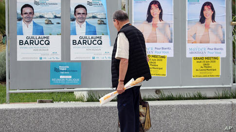 A man looks at posters advertising the upcoming local election, in Biarritz, southwestern France, Friday, June 26, 2020. The…