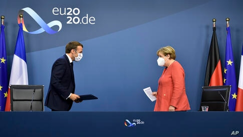 German Chancellor Angela Merkel, right, and French President Emmanuel Macron prepare to address a media conference at the end…