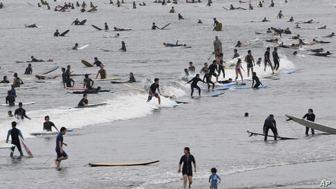 Surfers wait for a wave at a beach on a national holiday in Fujisawa, Kanagawa prefecture, near Tokyo, Thursday, July 23, 2020…