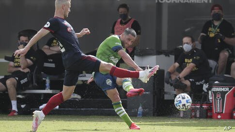 Seattle Sounders midfielder Nicolas Lodeiro, right, takes a shot on goal as Chicago Fire midfielder Fabian Herbers, left, tries…