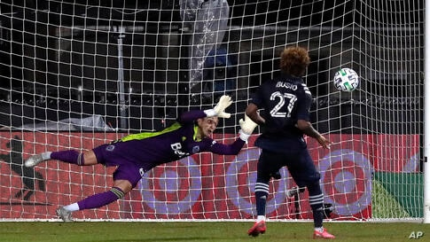 Sporting Kansas City forward Gianluca Busio (27) kicks the winning goal against Vancouver Whitecaps goalkeeper Thomas Hasal…