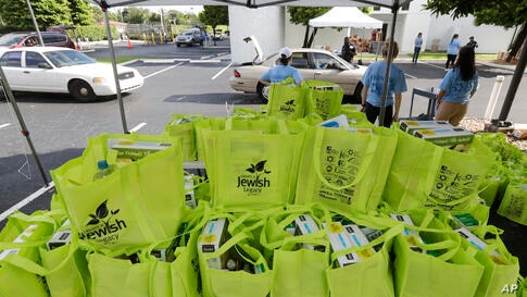 Volunteers handout food at a kosher food drive-thru distribution site, Wednesday, July 29, 2020, at the Greater Miami Jewish…