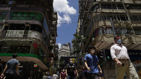 People wearing face masks to help curb the spread of the coronavirus walk on a downtown street in Hong Kong Tuesday, July 28,…