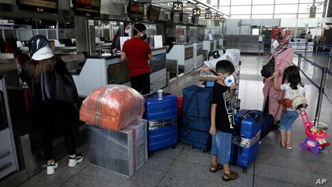 Passengers wearing protective face masks to help prevent the spread of the coronavirus check in at the Emirates airliner…