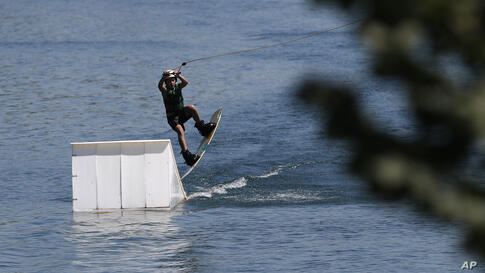 A man flies through the air as he wakeboards in the Ada Ciganlija Lake in Belgrade, Serbia, Wednesday, July 29, 2020. Hot…
