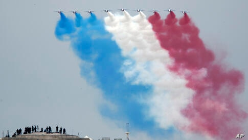 Guests watch form the top of the Arc de Triomphe the French Alpha jets of the Patrouille de France flying over the Champs…