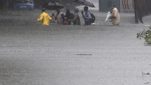 People navigate their way through a waterlogged street after their bus broke down during heavy rainfall in Mumbai, India,…