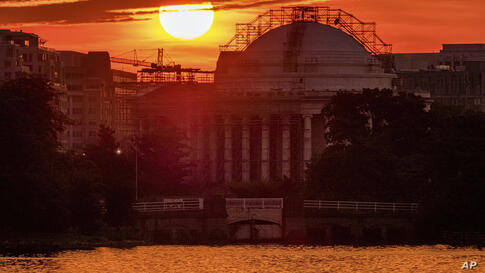 The sun rises behind the scaffolding clad Jefferson Memorial to begin a very hot day in Washington, Monday, July 20, 2020…