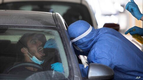 An Israeli man is tested by a healthcare worker for the coronavirus at a drive-thru testing center in Tel Aviv, Israel, Monday,…