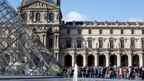 Visitors wait in the Louvre Museum courtyard prior to visit the museum, in Paris, Monday, July 6, 2020. The home of the world's…