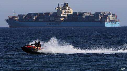 A man and a woman drive a jet-ski passes in front of a cargo ship during a warm day in southern coastal city of Limassol,…
