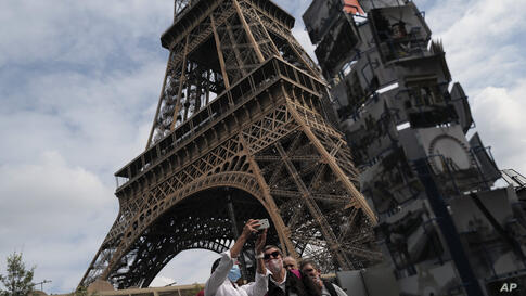 Visitors take a selfie at the main entrance during the opening up of the top floor of the Eiffel Tower, Wednesday, July 15,…
