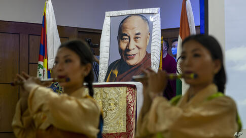 Exile Tibetan artists perform a special song to mark the 85th birthday of their spiritual leader the Dalai Lama whose portrait…