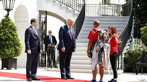 "President Donald Trump greets Terry Sharpe, known as the ""Walking Marine"" at the White House, Monday, July 27, 2020. Sharpe has…"