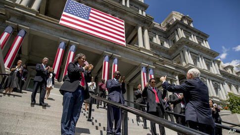 Vice President Mike Pence, right, gives two thumbs up as he speaks with 16 new Americans following a group photograph during a…