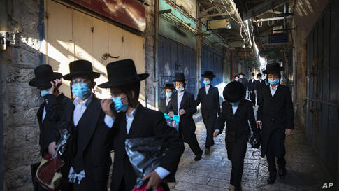 A group of ultra-Orthodox Jewish youth wear protective face masks following government measures to help stop the spread of the…