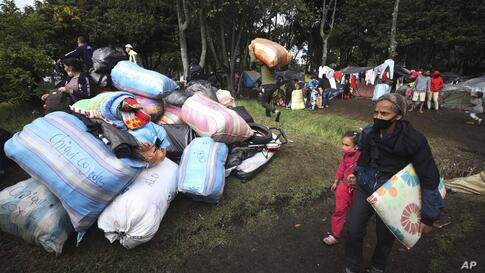 Venezuelan migrants, wearing protective face masks as a precaution against the spread of the new coronavirus, break camp in…