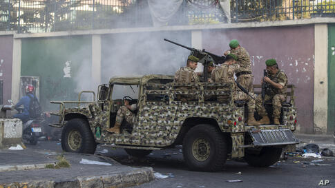 An army vehicle passes by garbage containers and tires that were set on fire by anti-government protesters to block the main…