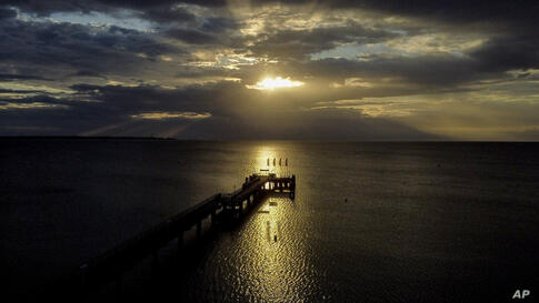 The rising sun is seen between clouds over the pier of Scharbeutz at the Baltic Sea, Germany, Monday, July 6, 2020. (AP Photo…