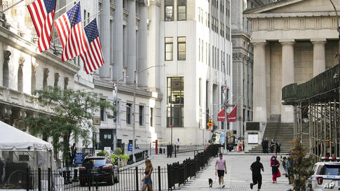 People walk by the New York Stock Exchange, left, Tuesday, July 21, 2020. Stocks are rising broadly on Wall Street in early…