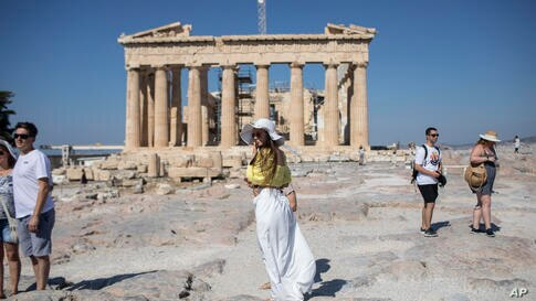 A woman poses for a photo, in front of the ancient Parthenon temple, at Acropolis Hill, during a hot day in Athens, Friday,…
