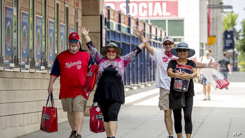Fans pose for a photograph as they leave the Washington Nationals team store at the Washington Nationals Stadium, Wednesday,…