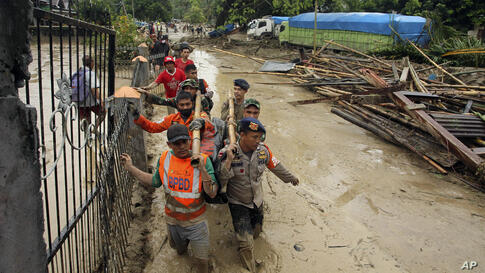 Rescuers wade through mud as they carry the body of a victim at an area affected by flash flood in Baebunta, South Sulawesi…