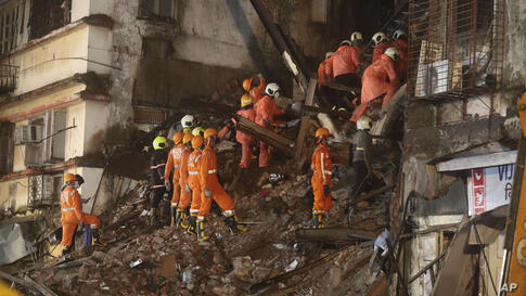 Rescuers work at the site after a six-storey residential building collapsed in Mumbai, India, Thursday, July 16, 2020. (AP…