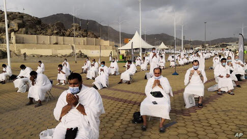 Muslim pilgrims pray near the Mercy mountain in Arafat as they distance themselves to protect against coronavirus during the…