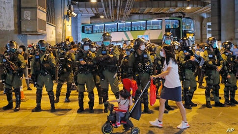 Riot police stand guard as pro-democracy protesters hold a news conference to mark one-year anniversary of the Yuen Long subway…