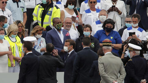 France's President Emmanuel Macron, wearing a face mask, bottom left, talks with health workers at the end of the Bastille Day…