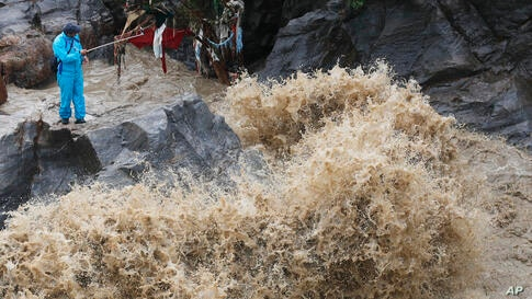A Nepalese man takes selfie on the banks of flooded Bagmati river in Kathmandu, Nepal, Tuesday, July 21, 2020. Landslides and…