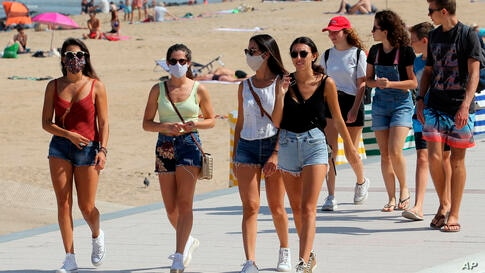 People wear face masks as they walk near the beach in Biarritz, southwestern France, Tuesday, July 21, 2020. Face masks are now…