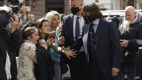 American actor Johnny Depp is greeted by fans as he arrives at the High Court in London, Tuesday, July 14, 2020.  Depp is suing…