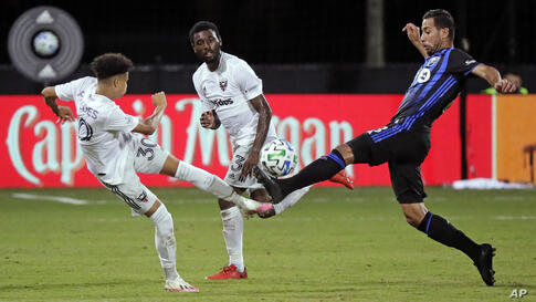 D.C. United midfielder Kevin Paredes, left, and Montreal Impact midfielder Saphir Taider, right, battle for possession as D.C…