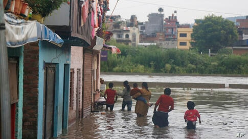 Nepalese people walk towards their flooded houses on the bank of the Bagmati river after water levels receded in Kathmandu, …
