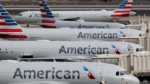 FILE - In this Wednesday, March 25, 2020, file photo, American Airlines jets sit idly at their gates as a jet arrives at Sky…
