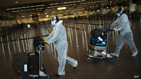 Passengers, wearing full protective gear to protect against the spread of coronavirus, push their luggage to check-in, as they…