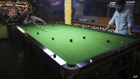 Two people play snooker at a game center in Kabul, Afghanistan, Thursday, July 23, 2020. (AP Photo/Rahmat Gul)