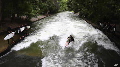 A surfer rides on an artificial wave in the river 'Eisbach' at the English Garden downtown in Munich, Germany, Thursday, July…