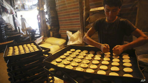 Vendors prepare sweets at a traditional bakery for the upcoming Muslim festival of Eid al-Adha in Kabul, Afghanistan, Thursday,…