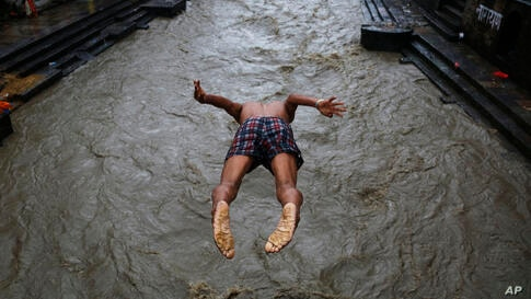 A Nepalese man jumps into the Bagmati river during monsoon rains in Kathmandu, Nepal, Monday, July 20, 2020. The weather…