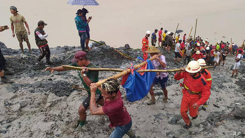 In this photo released from Myanmar Fire Service Department, rescuers carry a recovered body of a victim in a landslide from a…