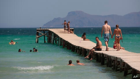 Sunbathers enjoy the beach in Alcúdia, in the Balearic Island of Mallorca, Spain, Tuesday, July 28, 2020. The U.K. government's…