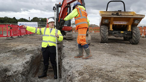Britain's Prime Minister Boris Johnson reads laser measurements during a visit to the Siemens Rail factory construction site in…