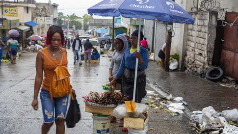 Street vendors and pedestrians stand in the rain brought by the outer bands of Hurricane Isaias in the Petionville district of…