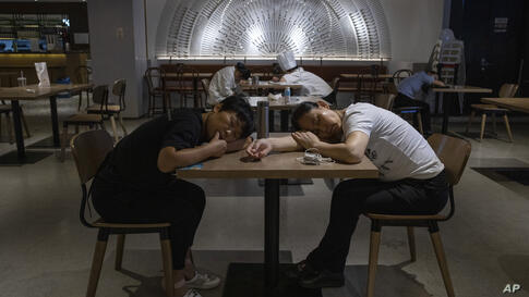 Restaurant workers nap on tables at a restaurant in a mall in Beijing on Wednesday, July 15, 2020. Small businesses around the…