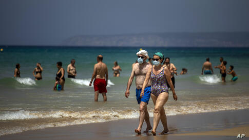 A couple wearing face masks walk along the shore in a beach in Cadiz, south of Spain, on Tuesday, July 21, 2020. (AP Photo…